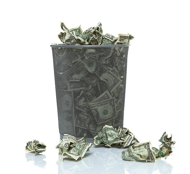 Trashcan full of money Trash can overflowing with money being thrown away money to burn stock pictures, royalty-free photos & images
