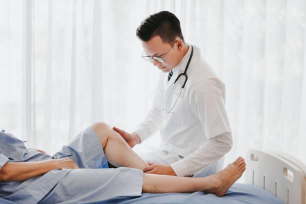 médico traumatologista examinando seu joelho paciente - ortopedia - fotografias e filmes do acervo