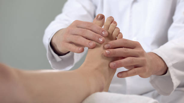 Traumatologist examining patient foot, rehabilitation procedures, leg fracture Traumatologist examining patient foot, rehabilitation procedures, leg fracture foot stock pictures, royalty-free photos & images