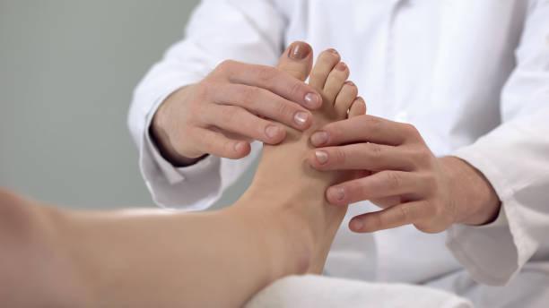 traumatologist examining patient foot, rehabilitation procedures, leg fracture - stopa zdjęcia i obrazy z banku zdjęć