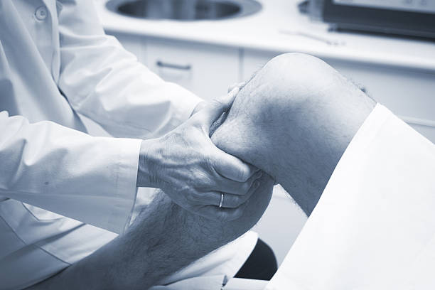 traumatologist orthopedic surgeon doctor examining patient - human knee stock photos and pictures