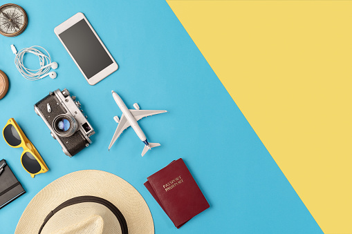 High angle view of travel accessories on the blue/yellow background with copy space