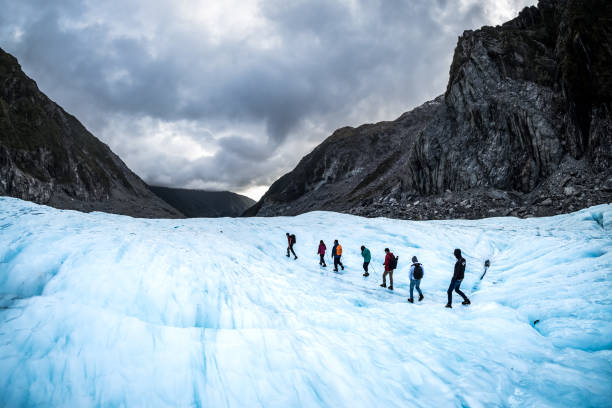 Travel adventure nature landscape image of hikers exploring Fox Glacier, New Zealand stock photo