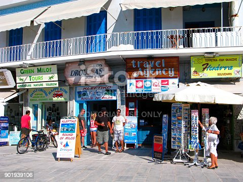 Greece, Cyclades, Milos island. Offices of travel agencies close to main port of island. Tourists visit travel agencies. Woman chooses souvenirs outdoor.