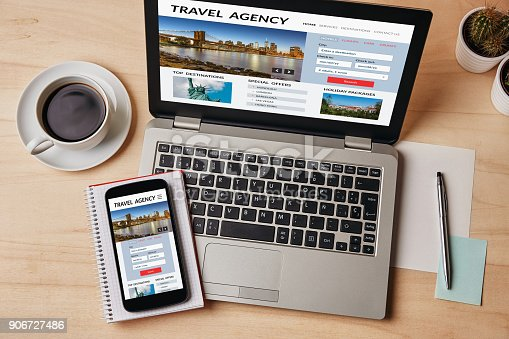 Travel agency concept on laptop and smartphone screen over wooden table. All screen content is designed by me. Flat lay