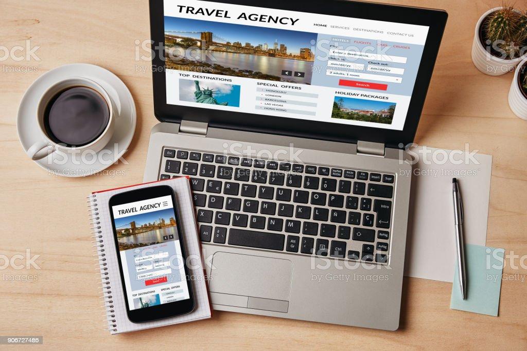 Concepto de agencia de viajes en la pantalla del ordenador portátil y smartphone - foto de stock