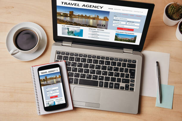 Travel agency concept on laptop and smartphone screen stock photo