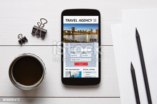 Travel agency concept on smart phone screen with office objects on white wooden table. All screen content is designed by me. Flat lay