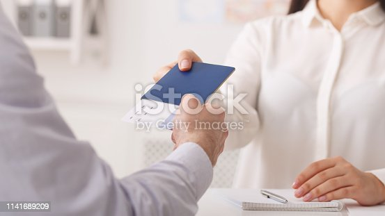 istock Travel agent giving passport with tickets to tourist 1141689209