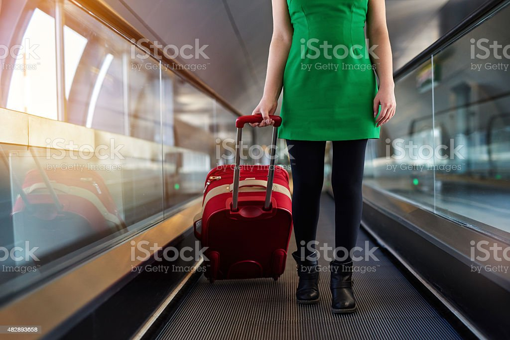 travel and carrying luggage woman legs carrying luggage in airport, traveling concept.wearing green dress, her luggage color is red, front view. 2015 Stock Photo