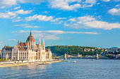 Travel and european tourism concept. Parliament and riverside in Budapest Hungary with sightseeing ships during summer sunny day with blue sky and clouds.