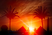 Travel and exploration, adventure. Holidays in Egypt. Archeology and history of the pharaohs, pyramids, obelisks, sphinxes and palm trees at sunset. Photograph the monuments. Sunset silhouette. 3d render