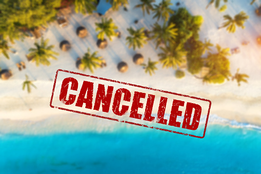 Travel and holidays cancelled due to epidemic of coronavirus. Tourism and resort cancelation due to Covid-19. Aerial view of beautiful tropical sandy beach, palm trees, blue sea in summer and text