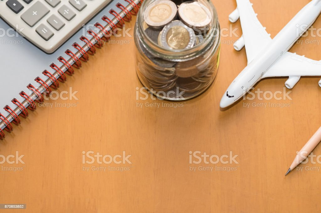 Travel and planning concept. Airplane toy model with full of coins in bottle, calculator, pencil and notebook, on wooden table. stock photo