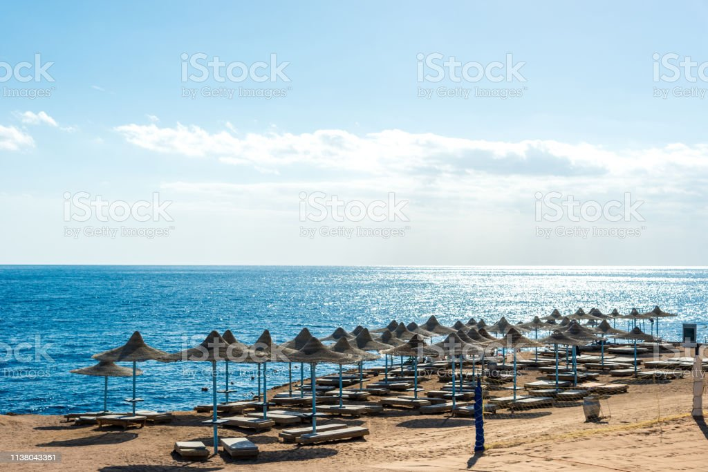 Travel and recreation, sun umbrellas, sun beds on the background of...