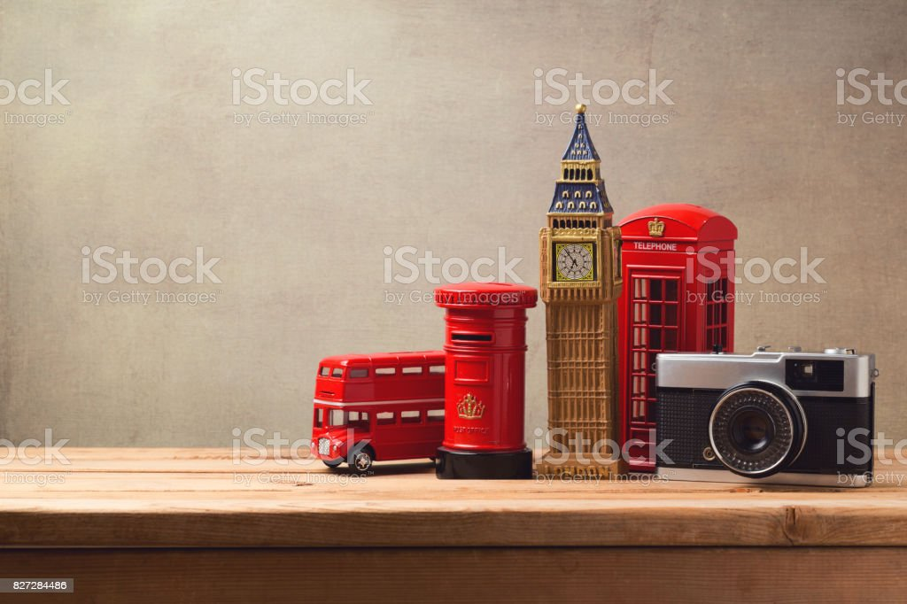 Travel and tourism concept with souvenirs from London and vintage camera on wooden table with copy space stock photo