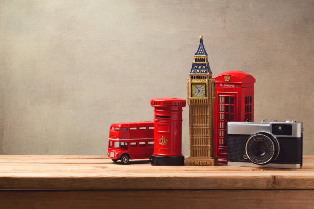 travel and tourism concept with souvenirs from london and vintage camera on wooden table with copy space - souvenir foto e immagini stock