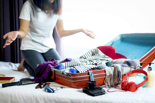 reisen und urlaub konzept, junge frau glück packen viele ihrer kleider und sachen in koffer auf bett bereiten sie reise- und reise reise im urlaub - gepäck verpackung stock-fotos und bilder