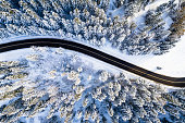 Travel background. Black road in white forest covered with snow. Aerial drone view. Mountain road. Winter landscape with highway.