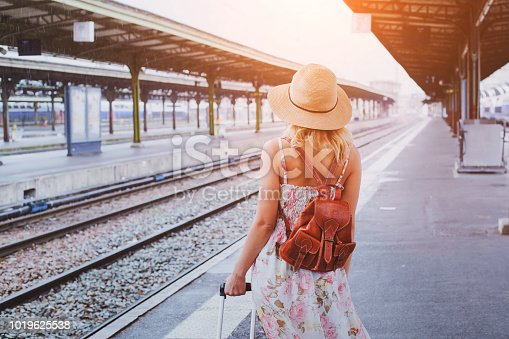 istock travel background, woman traveler with baggage, passenger waiting for the train on platform 1019625538