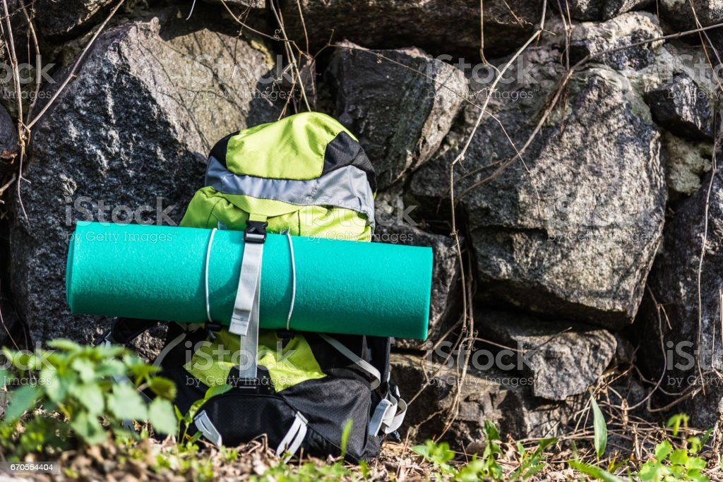 Travel backpack with touristic carpet on the awesome nature background. stock photo