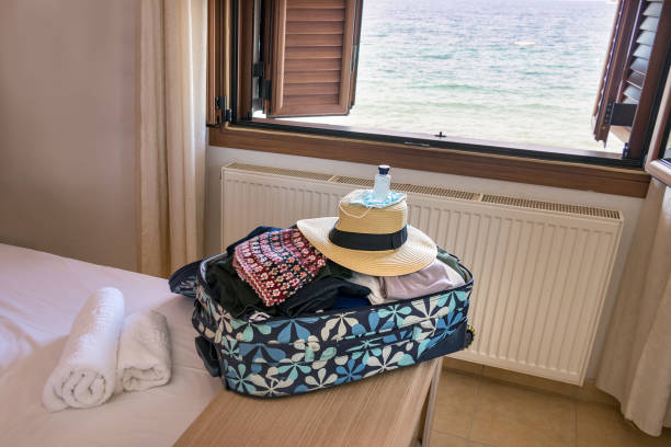 A travel bag with female clothes, straw hat, mask, hand sanitiser over a hotel room. stock photo