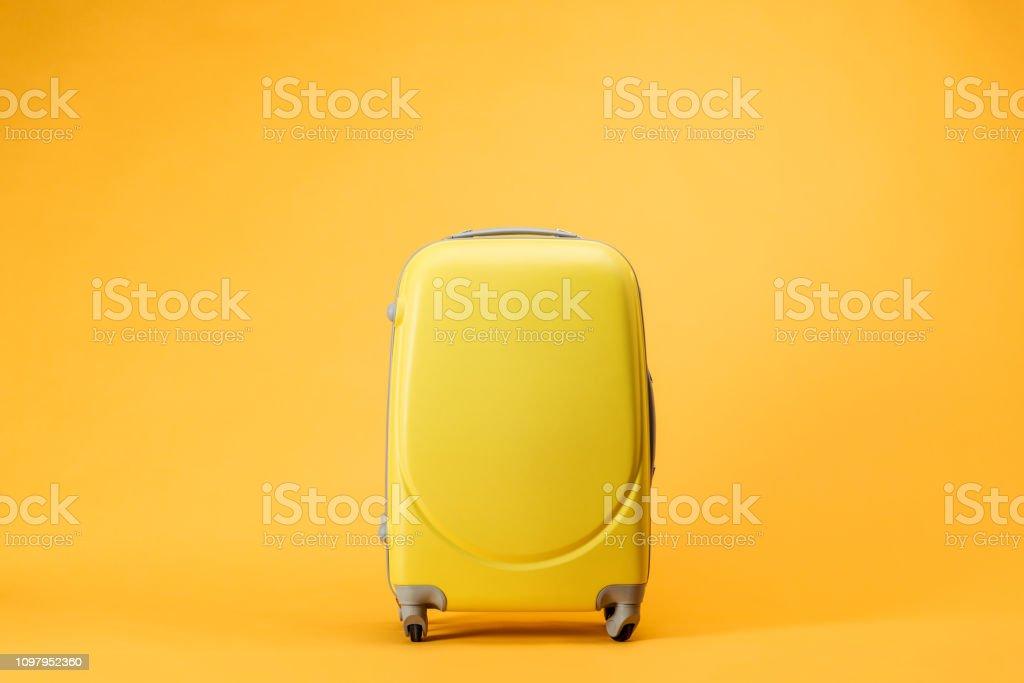 Reisetasche mit Rädern auf gelbem Hintergrund Lizenzfreies stock-foto