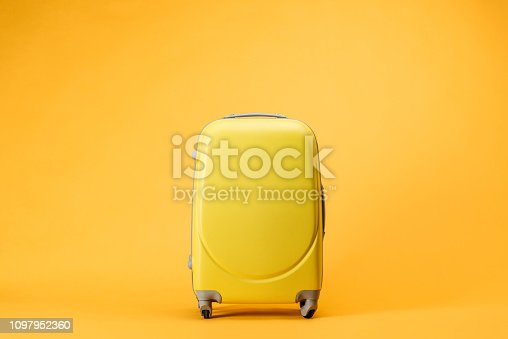 istock travel bag with wheels on yellow background 1097952360