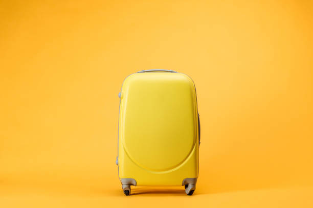 travel bag with wheels on yellow background - bagaglio foto e immagini stock