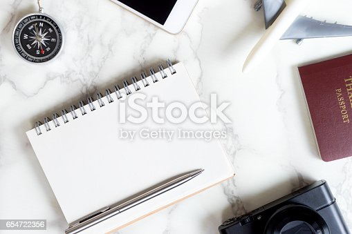 istock Travel blogger accessories on luxury white marble table with copy space on notebook 654722356