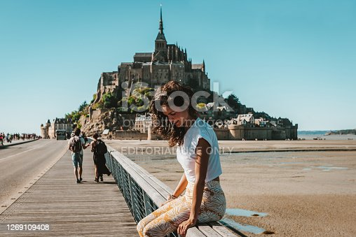 August, 4th, 2020 – Mont-Saint-Michel, France: Travel Blogger Sitting on Pont Passerelle at Mont-Saint-Michel. The Jetty Bridge is located in Normandy, France and was designed by Dietmar Feichtinger Architectes.
