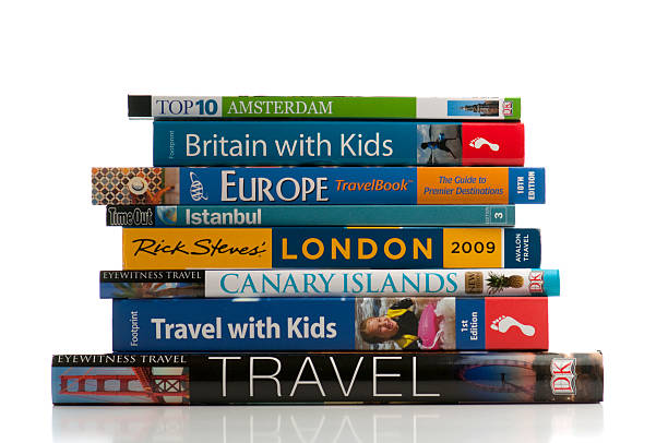 Travel books stacked in front of white background stock photo