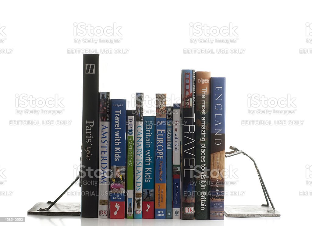 Travel books upright between bookends on white background royalty-free stock photo