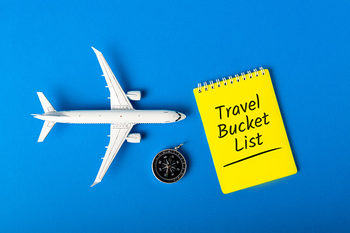 istock Travel Bucket list on blue background with compas and toy airplane. Trip Travel Destination and most visited places 1203932395