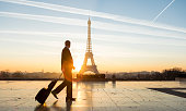 A beautiful sunrise takes place in Paris behind the iconic Eiffel Tower and a young businessman walks with his business luggage and contemplates the iconic monument. Concept of worldwide business travel, mobility and business confidence.