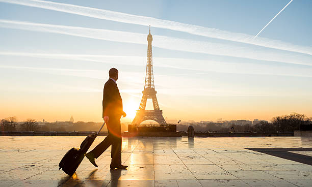 travel businessman walking with suitcase at eiffel tower in paris - business travel stock photos and pictures