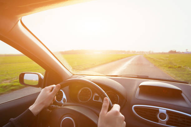 travel by car, hands of driver on steering wheel - car interior stock photos and pictures