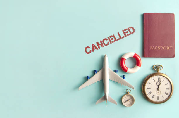 Travel cancellations Cancelled stamped by travel assessories including miniature airplane, clock and passport with space aground stock pictures, royalty-free photos & images