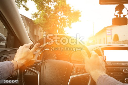 Travel car trip on road at sunset. Happy young man have fun driving inside vehicle in summer sunny day. Driver ride vacation concept