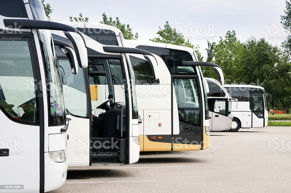 Travel coaches at tourist destination, parked in a row stock photo