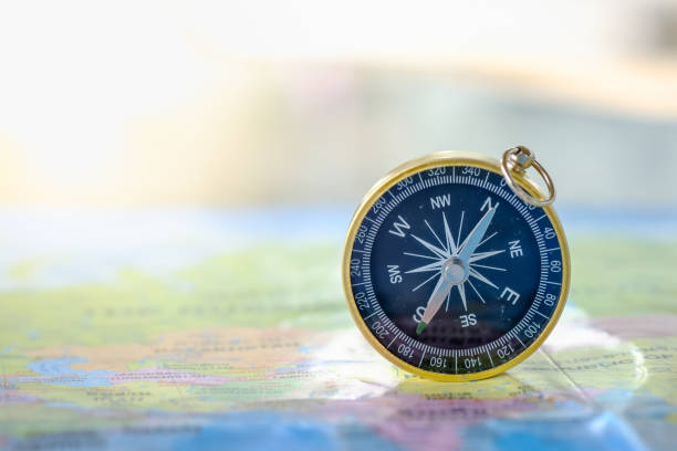 travel concept. close up of compass on world map. - globe navigational equipment stock photos and pictures