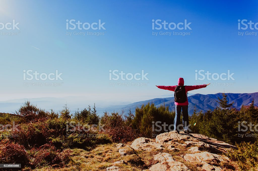travel concept- happy woman hiking in scenic mountains stock photo