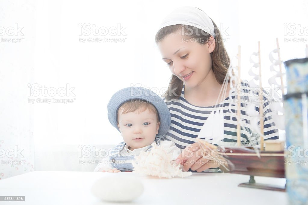 Travel concept. Mother and her baby boy with seashell. stock photo