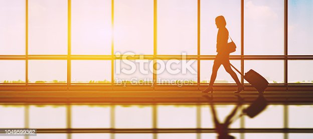 travel concept, people in the airports ,Silhouette of young girl with luggage walking at airport, women showing something through the window,selective focus,vintage tone color