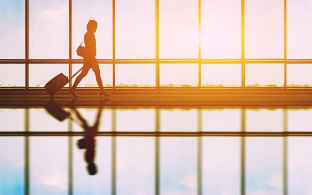 reisekonzept, Menschen in den Flughäfen Silhouette des jungen Mädchens mit Gepäck zu Fuß am Flughafen, Frauen zeigen etwas durch die Fenster, Tiefenschärfe, Vintage Klangfarbe – Foto