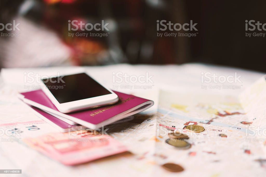 Travel concept Passports, smartphone, money and an open map on the desk. Some is sitting at the background. 2015 Stock Photo