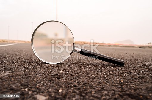 Travel Concept Magnify Glass Loupe on the Asphlat Road