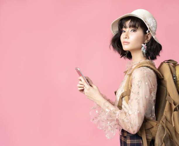 ピンクの背景で幸せな女アジア観光資源の宝庫の旅行コンセプトの肖像画 - 韓国文化 ストックフォトと画像