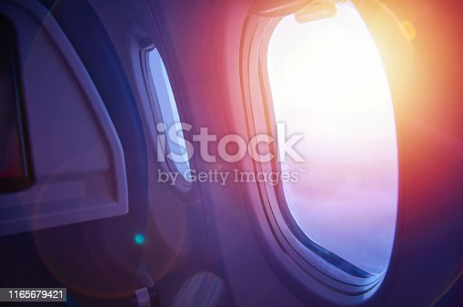 1045890176 istock photo Travel concept. Sunset through an airplane window. Plane interior. 1165679421