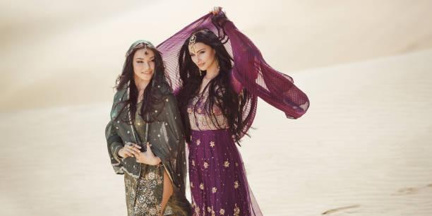 Travel concept. Two gordeous women sisters traveling in desert. Arabian Indian movie stars stock photo